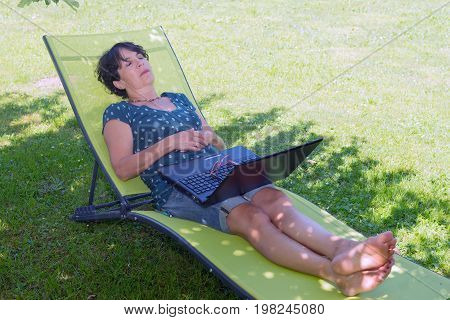 Happy mature woman relaxing resting on the deck chair in the garden