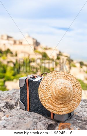 Nostalgic miniature straw hat and small decorative detailed suitcase at rock, french mountain village in background (copy space)