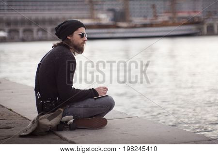 TRIESTE ITALY - MAY 14: Young man writing a diary seated on Trieste pier on May 14 2016