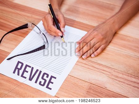 Digital composite of Revise  text written on page with wooden table