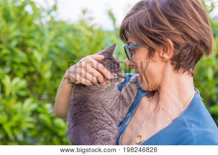 Playful Domestic Cat Held And Cuddled By Smiling Woman With Eyeglasses. Outdoor Setting In Green Hom