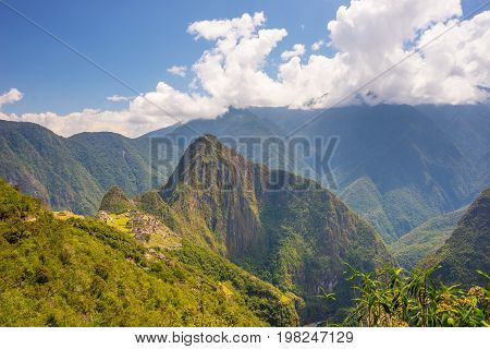 Machu Picchu archeological site and Wayna Picchu illuminated by the sunlight.
