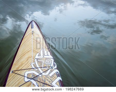Fort Collins, CO, USA - July 28, 2016: Expedition stand up paddleboard by Starboard on a calm lake.