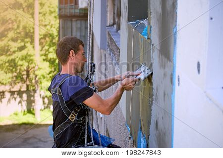 A man hanging on a rope performs work on the facade insulation.