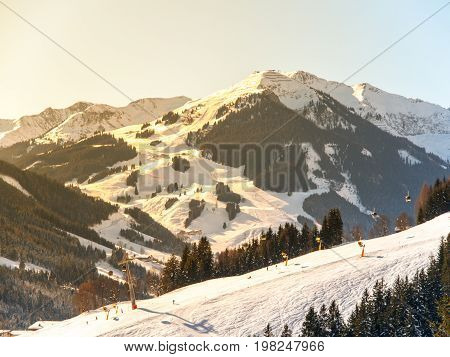 Downhill slope in Saalbach Hinterglemm Leogang winter resort, Tirol, Austria, Europe. Sunny morning with clear sky and illuminated mountain massive on the background.