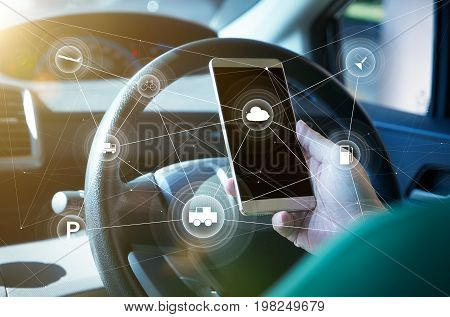 Man driver using smart self-driving car control system on a hand phone. Futuristic driving technology concept .
