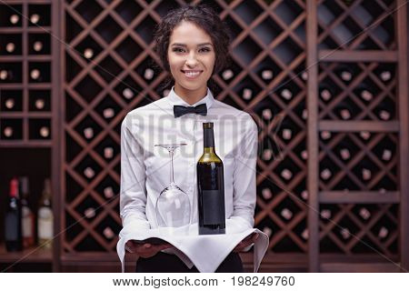 Close-up woman sommelier standing with bottle of wine and glass on tray in cellar
