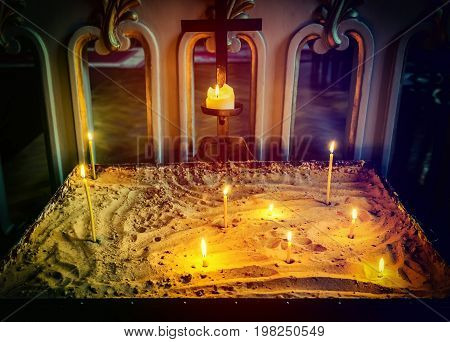 Candles on sandy pedestal inside of a church in old Riga
