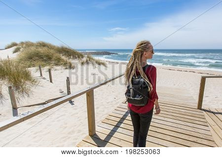 Young beautiful blonde girl with the dreads is on the path to the ocean.