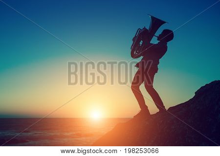 Silhouette at sunset of a musician play Tuba musical instrument on sea shore outdoor.