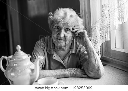 An elderly woman, a black-and-white portrait in the kitchen sitting at the table.