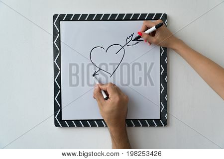 A guy and a girl draw a heart with markers on a white board. A mask and a female hand against a white board with a symbol of love.