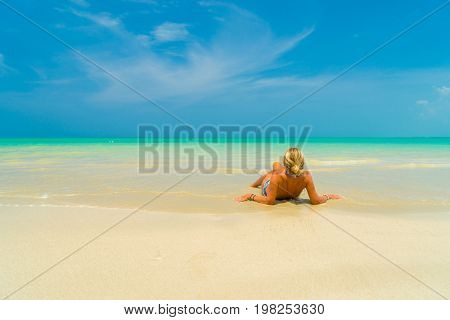 Woman laying on the sand on a beautiful tropical  beach