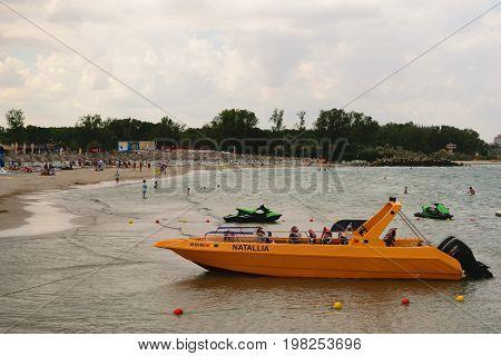 Neptun Romania - July 8 2017: Yellow speed boat for tourism. People having fun at the beach resort in Neptun Constanta Romania Europe