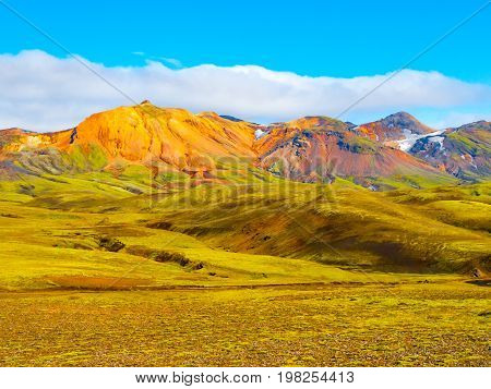 Green hills and black rocky ground of Icelandic Highlands along Laugavegur hiking trail, Iceland. Sunny summer day shot.
