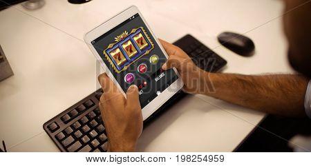Casino slot machine app on mobile screen against businessman using digital tablet in office