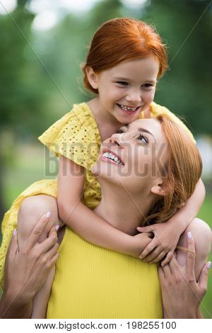 Mother Carrying Daughter Daughter On Shoulders