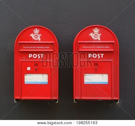 Falster. June-14-2017. Two danish red postbox on the black wall.