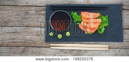 Close up of salmon in plate against full frame of wooden wall
