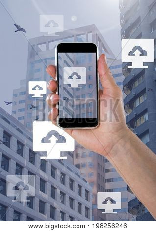 Digital composite of Holding phone and Computer cloud upload icons in city