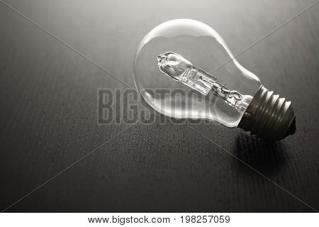 Incandescent Light Bulb on a Wooden Background
