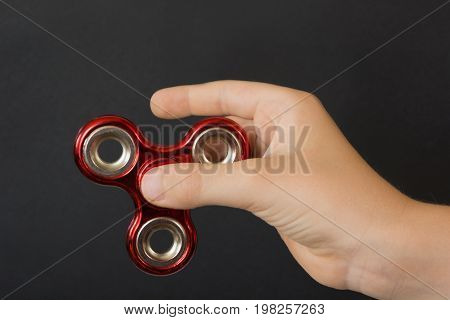 Fidget red spinner stress in childs hand on black.