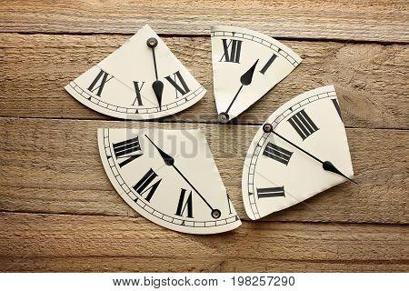 Broken Pieces of Clock on Wooden Background