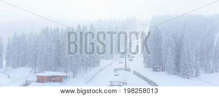 Panorama banner of ski resort during snowfall, ski lift, skiers, snowy trees at winter time