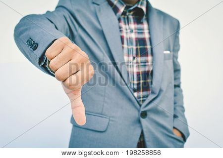 Close up of hand businessman thumbs down on blue background