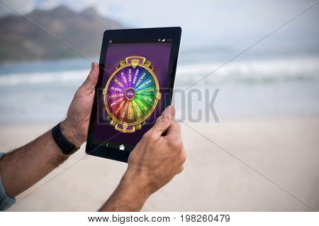 Multi colored fortune of wheel on mobile display against cropped image of man using tablet