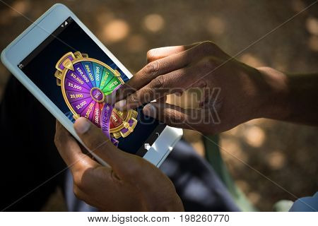 Colorful wheel of fortune on mobile display against man using tablet computer
