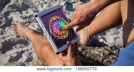Multi colored fortune of wheel on mobile display against man using digital tablet on the beach