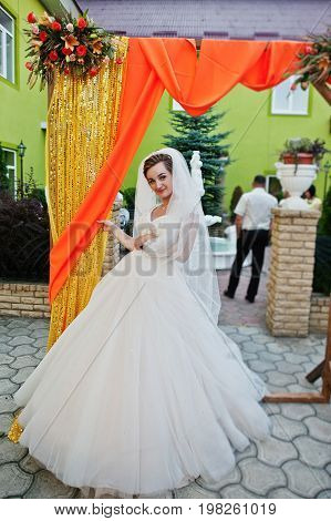 Flawless Young Bride In Gorgeous White Wedding Gown Posing Next To The Decorated Arch.