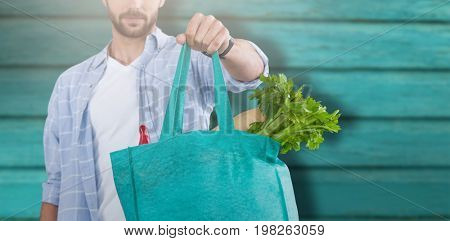 Midsection of man holding bag with vegetables against full frame shot of turquoise wall
