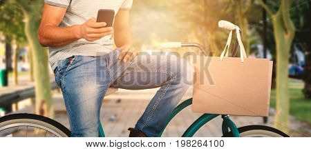 Man using phone while sitting on bicycle against footpath amisdt treelined