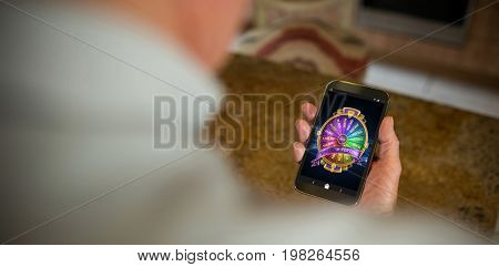 Colorful wheel of fortune on mobile display against cropped image of man holding phone