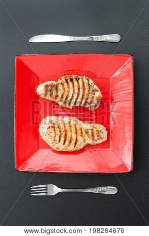 Juicy roasted pork loin on red plate