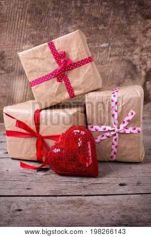 Gift boxes and decorative heart on vintage wooden background. Selective focus. Place for text.