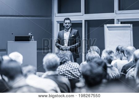 Speaker giving a talk at conference meeting business event. Audience at the conference hall. Business and Entrepreneurship concept. Black and white blue toned image.