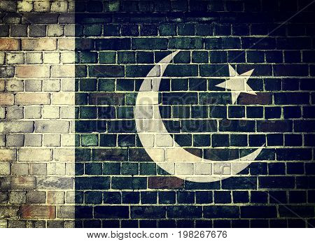Faded Pakistani flag on an old brick wall background with a dark vignette