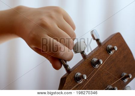 Photo of girl's hand tuning guitar close-up