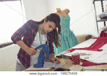 Young dressmaker working in her atelier putting buttons on the fabric