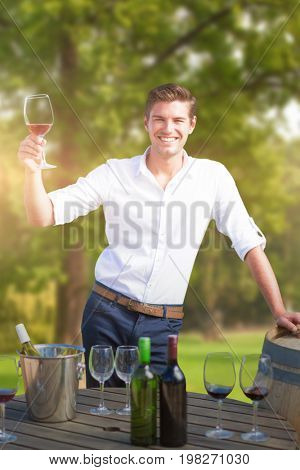 Portrait of smiling young man holding red wine glass by barrels against trees and meadow