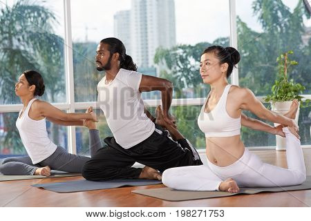 Group of people practicing king pigeon position in yoga studio
