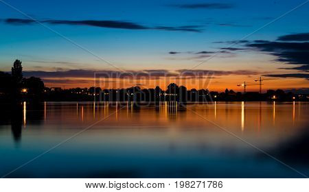 skyline with a blue sky and a red area close to the horizon; reflections on the water in the foreground