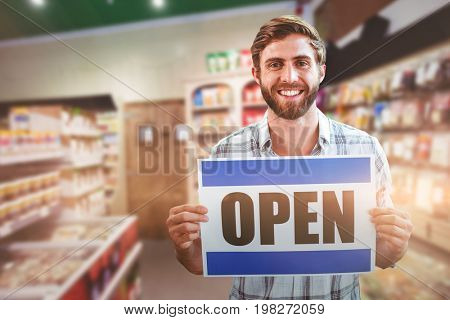 Portrait of happy male owner holding open sign against defocused image of food products