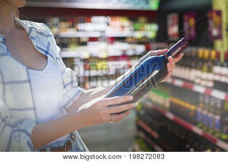 Mid section of woman holding wine bottle against wine bottles arranged on shelves