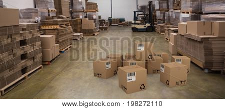 Group of composite cardboard boxes against forklift in a large warehouse