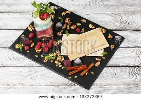 A top view of two postcards on a stone substrate and on a gray wooden background. A multicolored cocktail with fresh mint, cinnamon sticks, walnuts and berries on the table. Celebration concept.