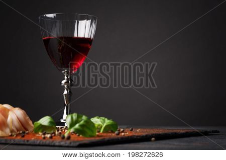 A full wineglass, jerked meat and spicy basil on a saturated black background. A great composition of salty food or snacks on the dark table. Tasty prosciutto and red wine. Copy space.